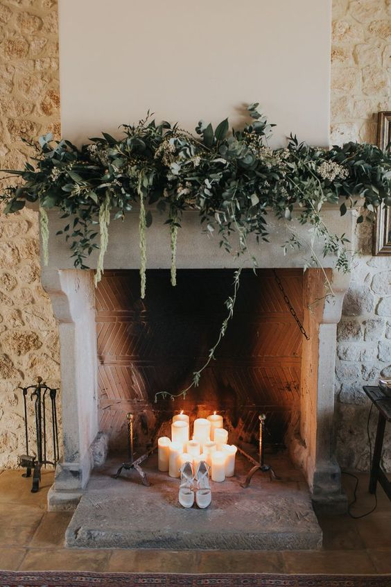 pillar candles in the fireplace and a lush greenery and white bloom decoration on the mantel make the fireplace super cool