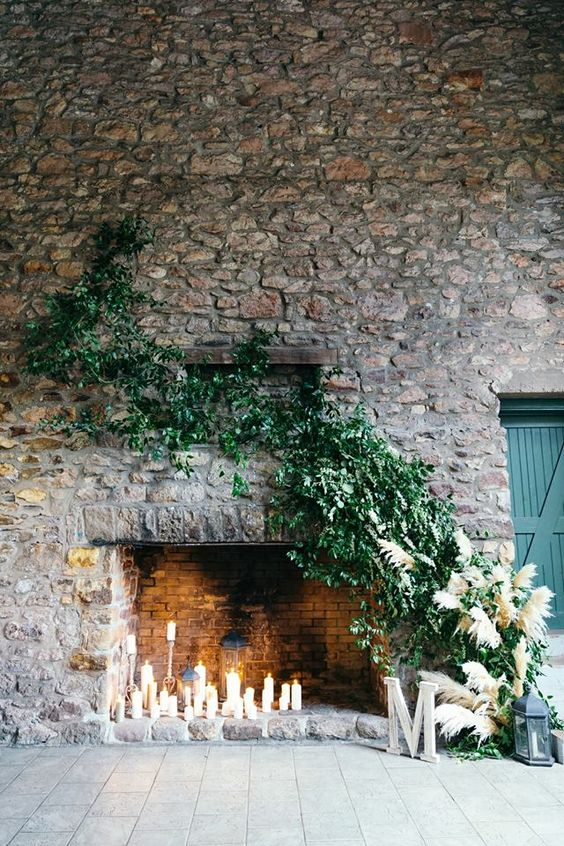 pillar candles in the fireplace, greenery and pampas grass climbing up the stone wall for a refined and cozy feel