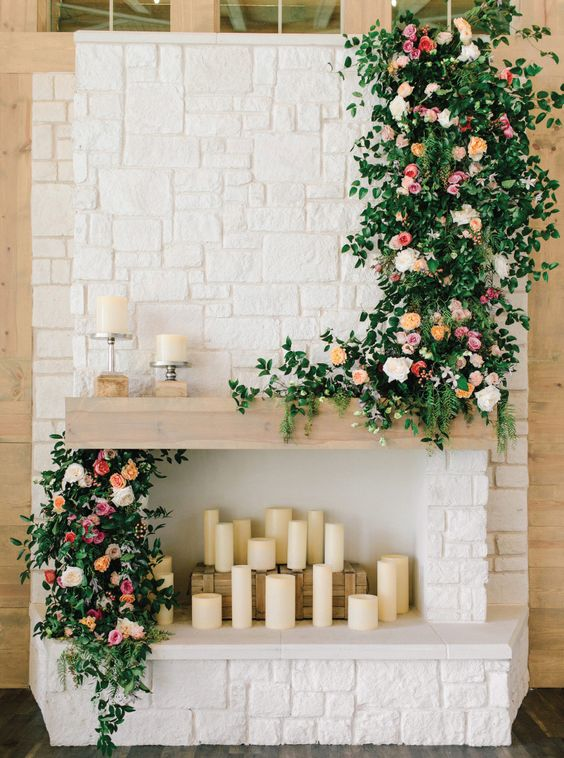 pillar candles, lush greenery and pink blooms make the fireplace chic and very beautiful, a perfect wedding backdrop