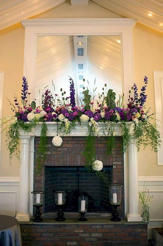 purple and white blooms, greenery hanging don and soem greenery arrangements plus candles in vintage glasses