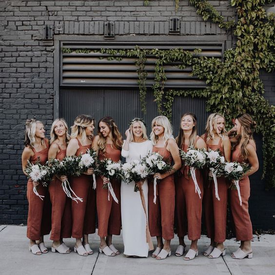 rust-colored bridesmaid jumpsuits with square cuts and cropped pants, white mules and white bouquets for a boho wedding
