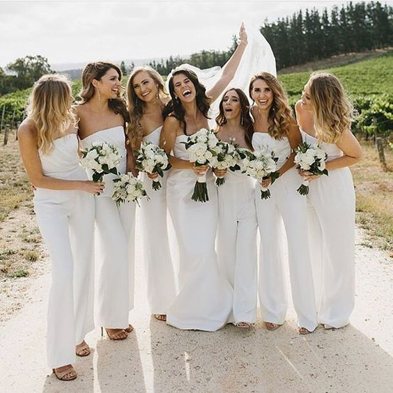 strapless white jumpsuits with draped bodices is a bold and chic idea for a summer wedding with a touch of edge