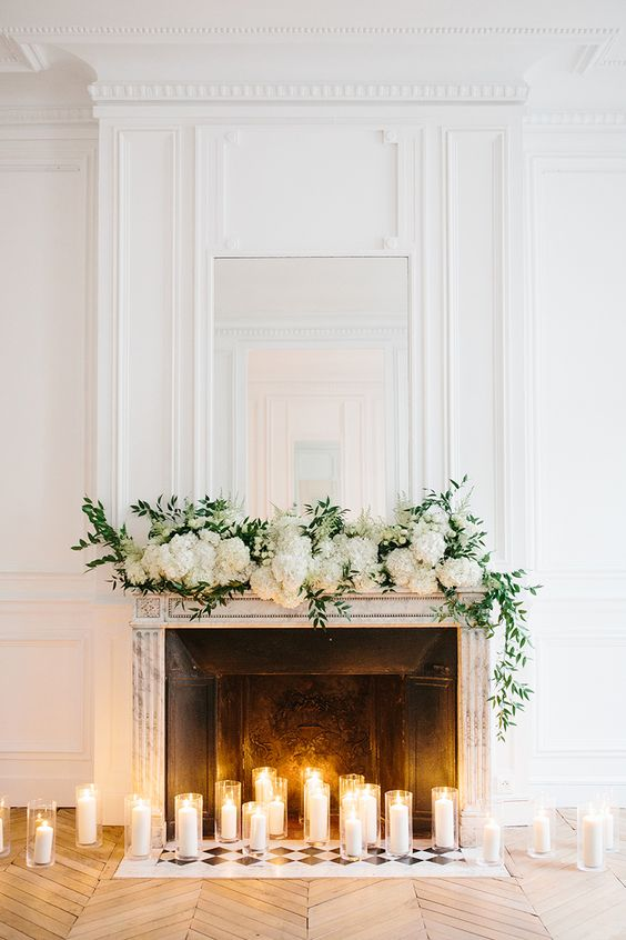 tall candles in glasses and greenery plus lush white hydrangeas make the fireplace look very elegant and very chic