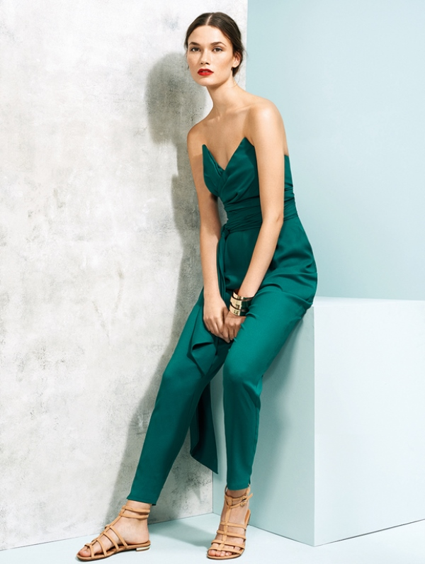 a fitting strapless emerald jumpsuit with a sculptural draped bodice and nude sandals for a bright bridesmaid look