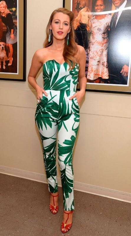 a strapless fitting jumpsuit with a tropical print, red shoes and statement earrings for a summer or tropical wedding