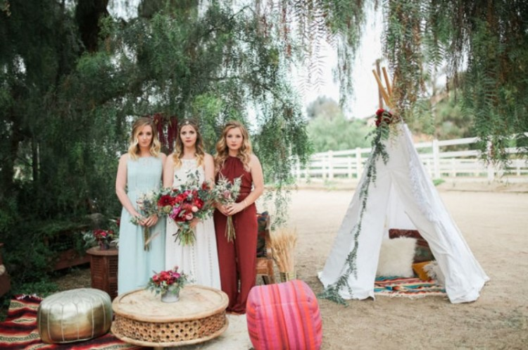 a halter neckline burgundy jumpsuit is a cool idea for a fall boho wedding