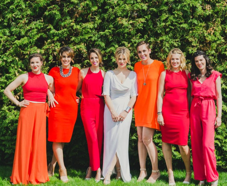 mismatching fuchsia-colored bridesmaid jumpsuits with sashes and pockets for a colorful summer wedding