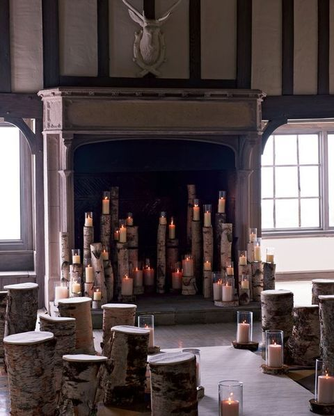 tree stumps and branches with candles in glasses on top placed into the fireplace make it look very woodland-like