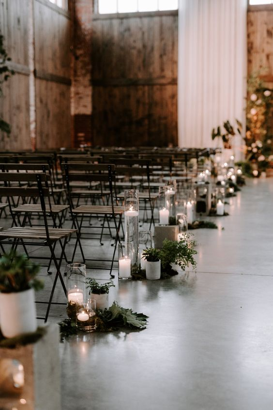 white curtains for a backdrop and aisle decor with greenery and candles for a modern industrial wedding space