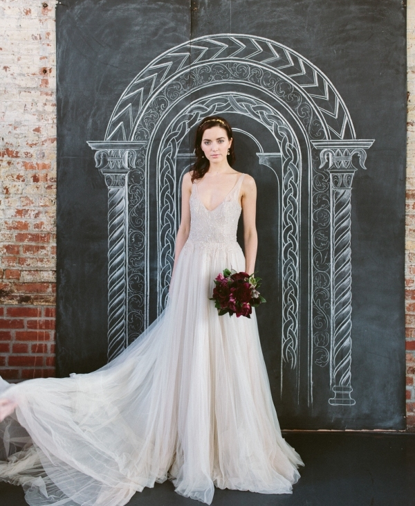 an A-line off-white wedding dress with an embellished bodice, a deep neckline, no sleeves and a layered skirt with a train