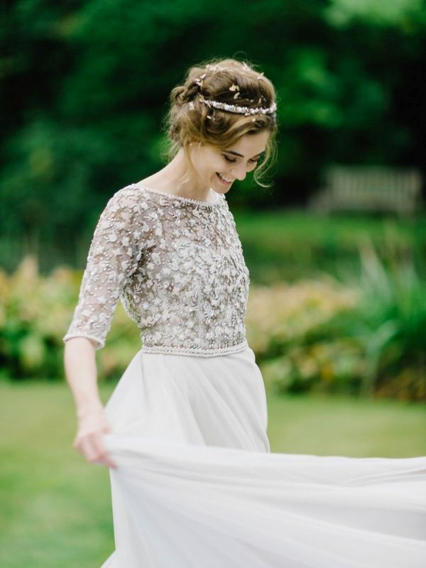 a modern wedding look with a grey embellished and applique bodice with short sleeves and a neutral layered skirt