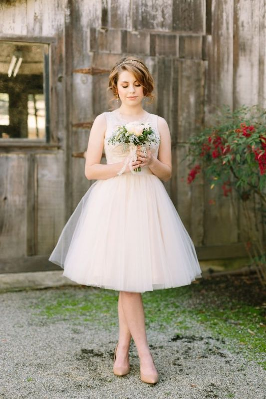 an A-line knee sleeveless wedding dress with an illusion neckline and a full skirt for a ballerina-like look
