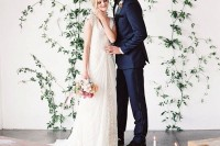 an ethereal and chic greeenery wedding backdrop indoors – some greenery branches attached right to the wall and greenery lining up the aisle