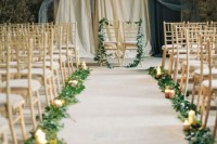 a romantic wedding backdrop of various textiles, a couple of chairs with greenery, greenery and candles lining up the aisle