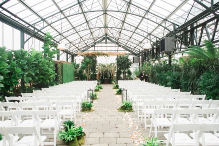 a lush greenery wedding space with foliage and greenery and white blooms hanging down, greenery and petals to line up the aisle