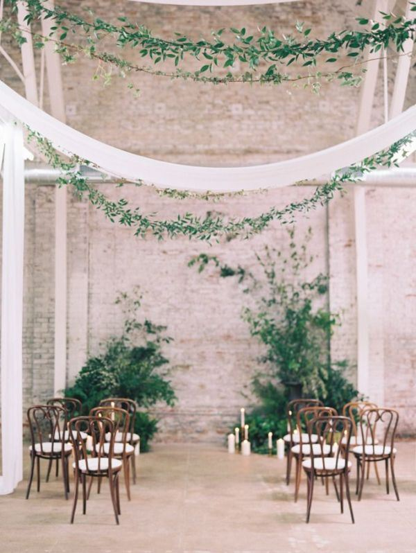 a romantic botanical wedding ceremony space with lush greenery, candles, greenery garlands and neutral textiles over the space