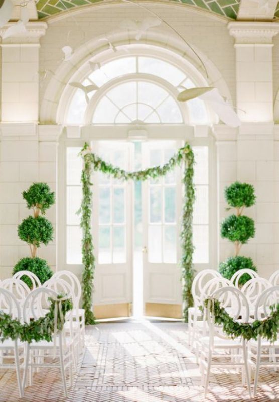 a refined romantic wedding ceremony space with a greenery garland attached to the doorway, greenery topiaries and greenery garlands on the chair
