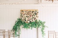 a beautiful and lush botanical wedding backdrop with greenery on the mantel, a lush floral artwork in a frame and greenery on the aisle for a chic look