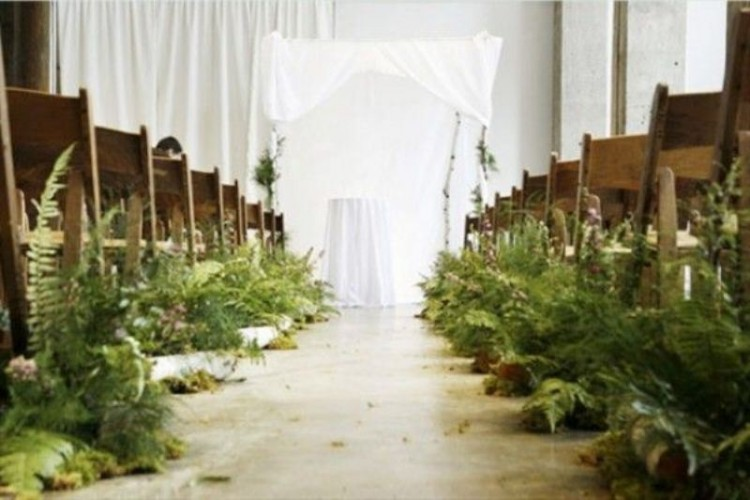 a botanical wedding ceremony space with white textiles and lush ferns lining up the aisle to make it look woodland-like