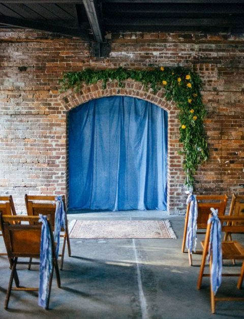 a blue denim backdrop paired with greenery and yellow blooms and denim ribbons on the chairs for a casual or industrial wedding