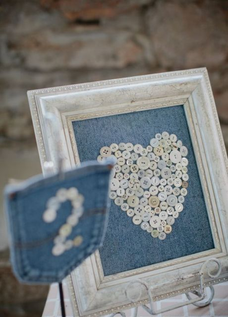 a denim artwork of buttons in a neutral frame and a pocket with a table number of buttons for a cowboy wedding