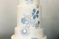 a white wedding cake with blue floral and other decor that reminds of traditional denim colors
