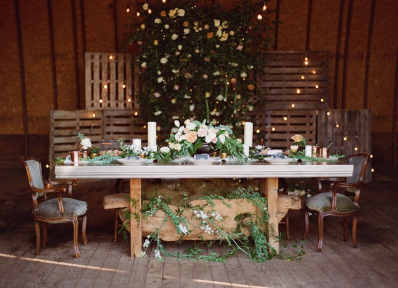 a reception space decorated with wooden screens with lights, greenery and neutral blooms, greenery runners and a decoration under the table