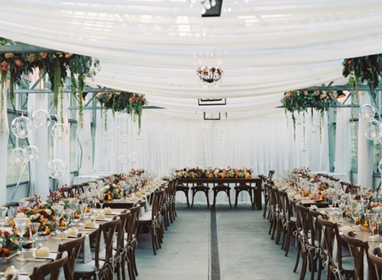 greenery and bright blooms over the tables and bold blooms on the tables make the space lovely and welcoming