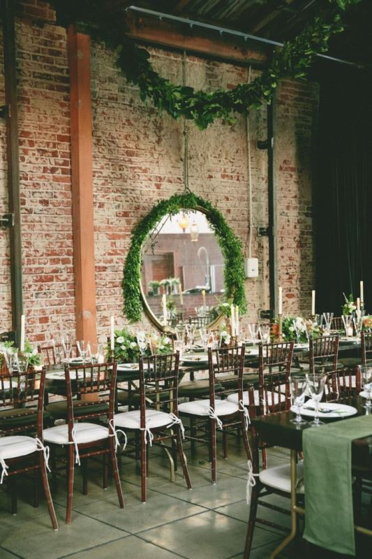an industrial wedding venue with brick walls, a greenery garland and a mirror covered in greenery and greenery and white bloom centerpieces