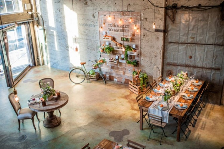 an industrial reception space with shabby walls, bulbs, and greenery and bright blooms that enliven and soften the decor