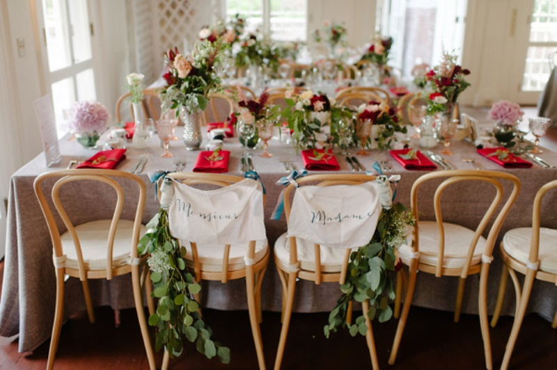 bright blooms and greenery centerpieces and greenery chair decor make the reception space cozier