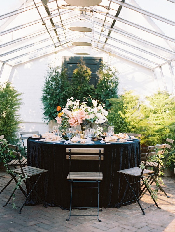 a fresh wedding venue with potted greenery all over, a pastel floral centerpiece looks catchy and cool