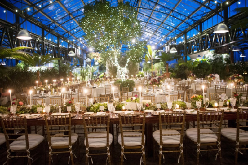 an eye catchy and charming wedding reception with potted greenery and trees, greenery chandeliers with lights and greenery and bloom runners
