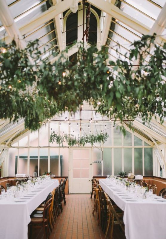 a simple and elegant wedding reception space with greenery hangings over the space and white linens is chic and elegant