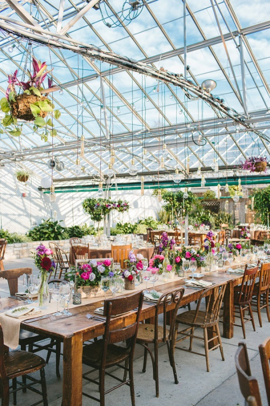 a bold and chic wedding reception space with potted greenery, hanging arrangements and kokedama, bright florals on the table