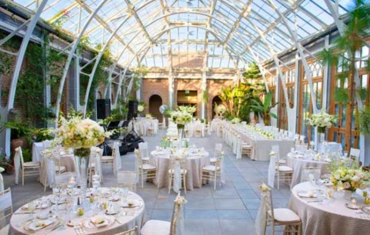 an elegant and refined wedding venue with greenery climbing up the walls, neutral and pastel blooms for centerpieces