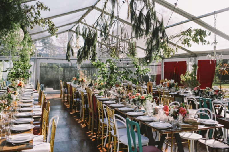 a botanical wedding venue with greenery hanging over the space, burgundy curtains, bold blooms and mismatching chair for a touch of fun