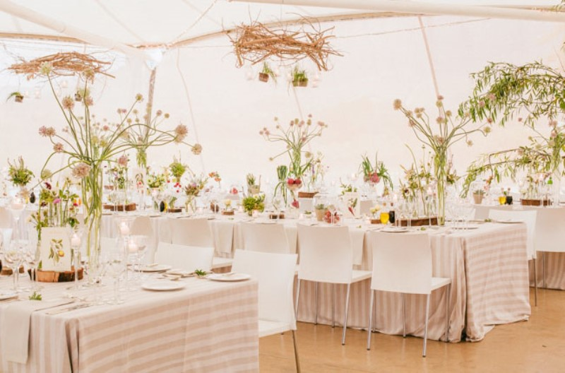 a cool botanical wedding reception space decorated with vine chandeliers, pink blooms and greenery and colorful pots to make the space whimsy