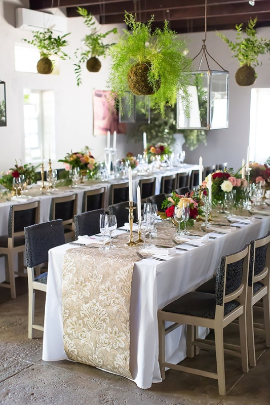 a beautiful wedding reception space with bright blooms and greenery on the table and kokedama balls hanging over the space and a greenery arrangement in the corner