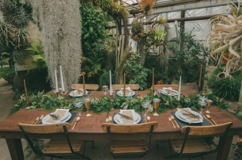 a botanical wedding reception space with lots of gorwing bushes and plants, grasses and hanging plants, greenery runners to match the space