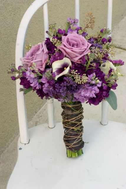 a bright wedding bouquet of purple and lilac blooms and greenery with a twine wrap to give a rustic feel to the bouquet