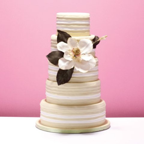 a striped wedding cake decorated with a large magnolia bloom and dark leaves is a cool idea for a chic wedding