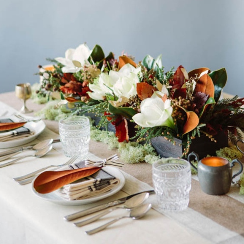 a creative wedding centerpiece of a box and some greenery and magnolia leaves and blooms is a chic decor idea