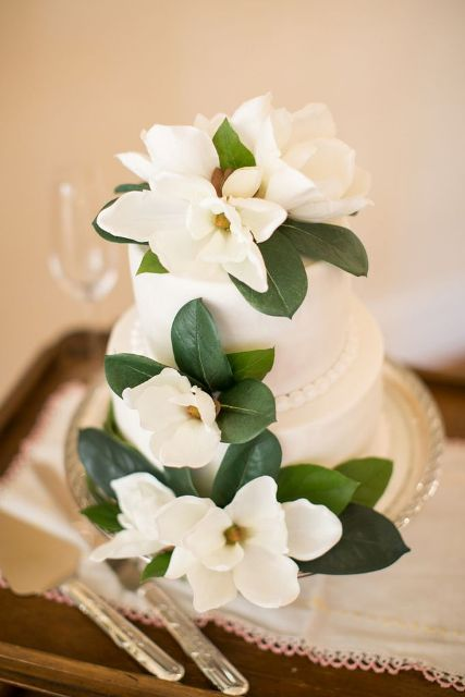 a white wedding cake decorated with magnolia flowers is a very elegant and chic idea