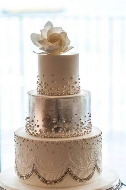 a glam white and silver wedding cake decorated with white and silver beads and a single magnolia bloom on top