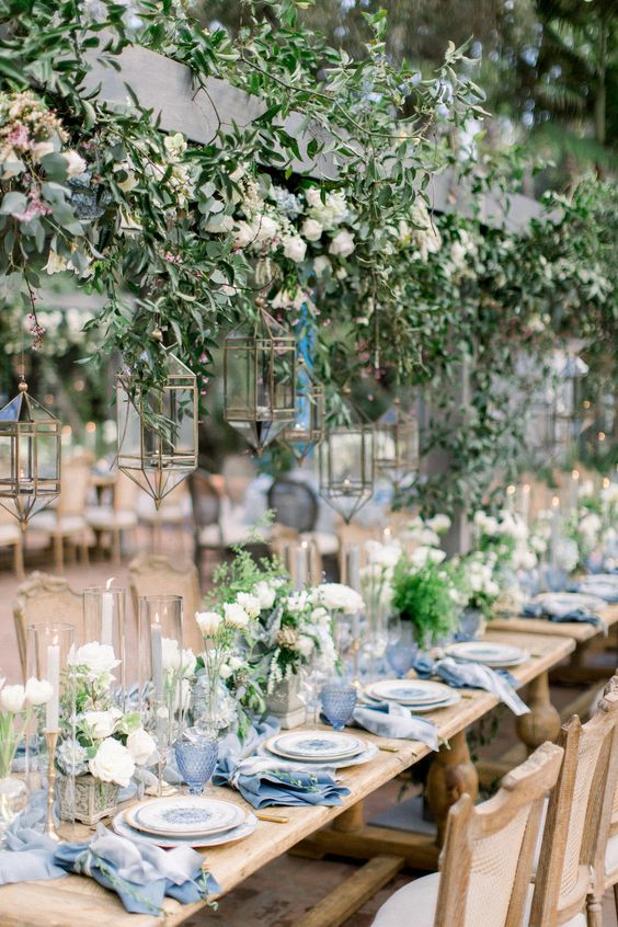 a beautiful botanical wedding venue with hanging greenery and white blooms, candle lanterns, white floral centerpieces and blue linens