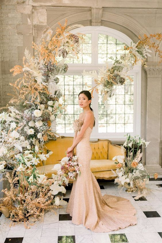 a beautiful pastel wedding backdrop of white and blush blooms, of greenery, dried fronds and leaves is a lush and chic idea