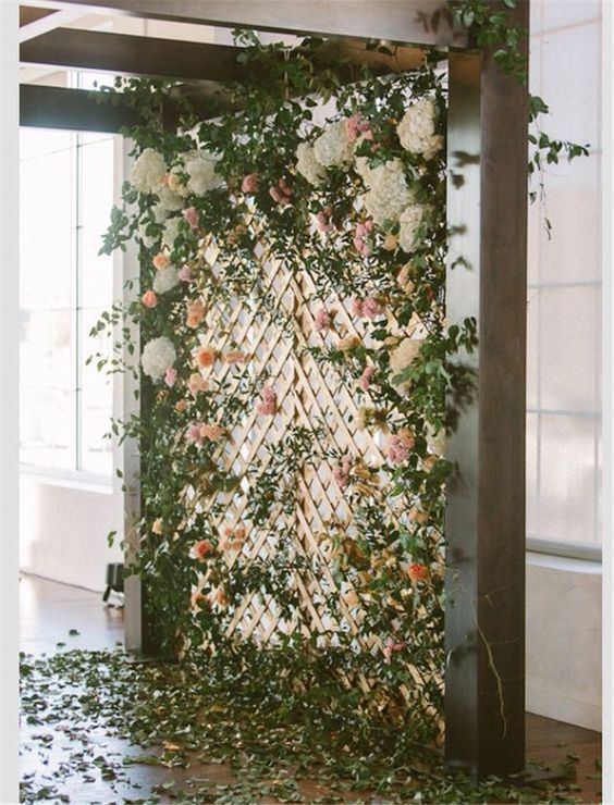 a beautiful wedding backdrop of greenery, pink, peachy and white blooms, foliage on the floor for indoors