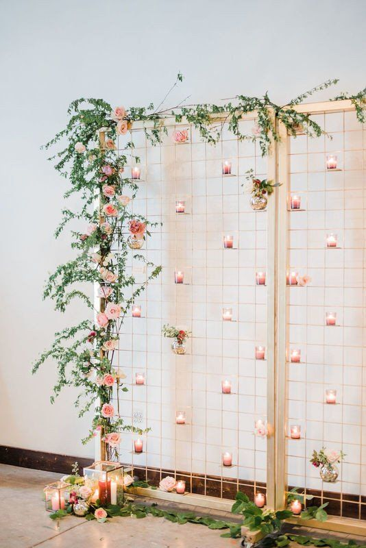 a beautiful wedding backdrop with greenery, pink blooms and pink candleholders attached all over the backdrop is a lovely idea