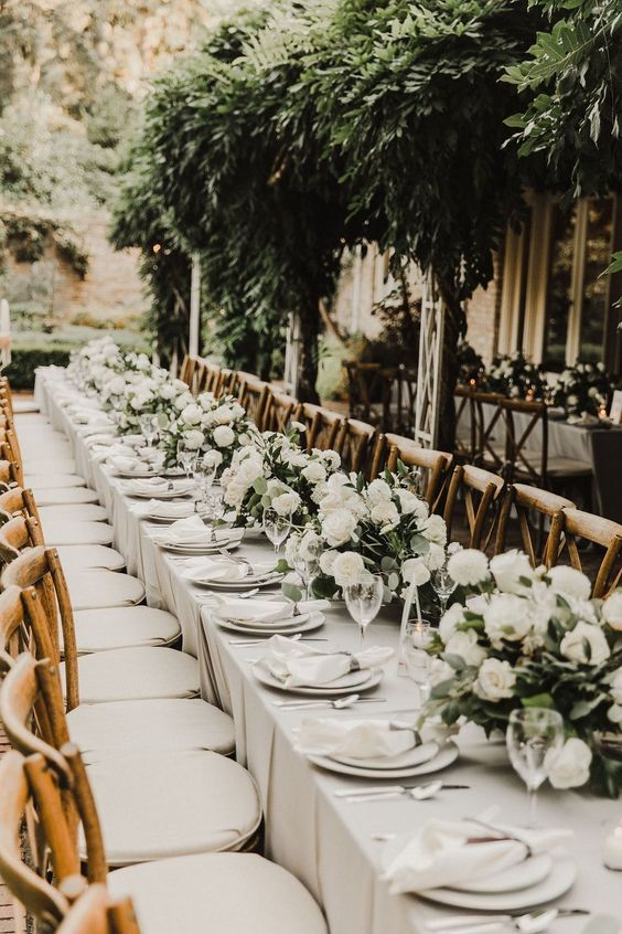 a beautiful wedding reception space with a greenery installation and white floral centerpieces looks very stylish and chic